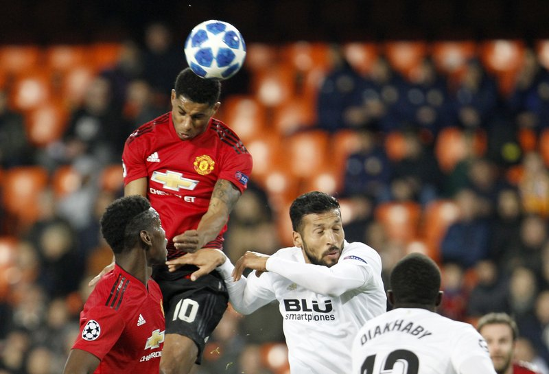 Manchester United's Marcus Rashford, second left, jumps for the ball with Valencia defender Ezequiel Garay, third left, during a Group H Champions League soccer match between Valencia and Manchester United at the Mestalla Stadium in Valencia, Spain, Wednesday, Dec. (AP Photo/Alberto Saiz)