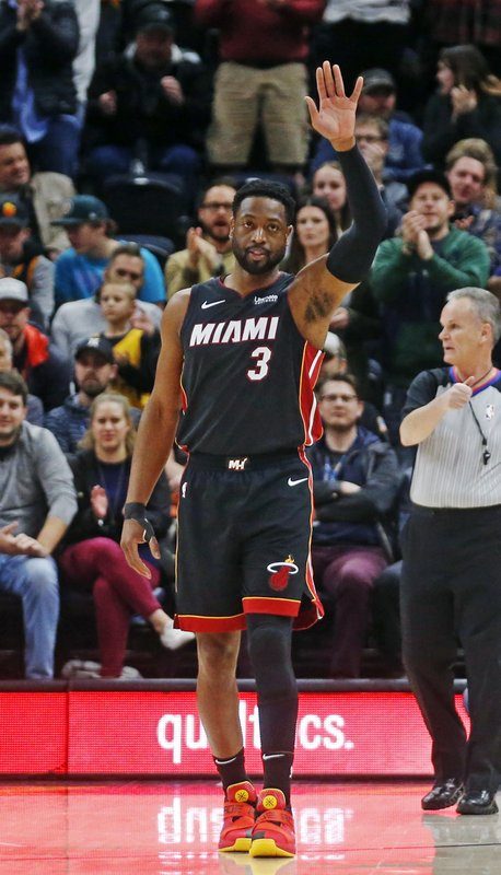 Miami Heat guard Dwyane Wade (3) waves to the fans as he is introduced in the first half of an NBA basketball game against the Utah Jazz, Wednesday Dec. (AP Photo/Rick Bowmer)