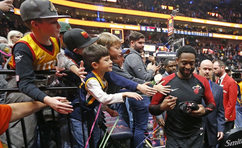 Miami Heat guard Dwyane Wade signs autographs for fans following their NBA basketball game against the Utah Jazz Wednesday Dec. (AP Photo/Rick Bowmer)