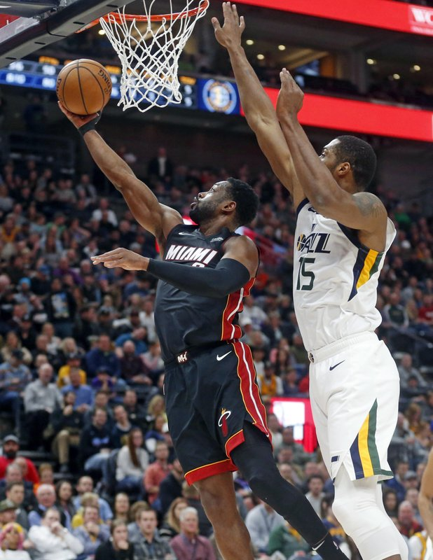 Miami Heat guard Dwyane Wade (3) lays the ball up as Utah Jazz forward Derrick Favors (15) defends in the first half during an NBA basketball game, Wednesday, Dec. (AP Photo/Rick Bowmer)