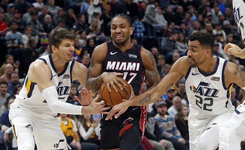 Utah Jazz's Kyle Korver (26) and Thabo Sefolosha (22) defend against Miami Heat forward Rodney McGruder (17) as he drives to the basket in the first half of an NBA basketball game, Wednesday Dec. (AP Photo/Rick Bowmer)