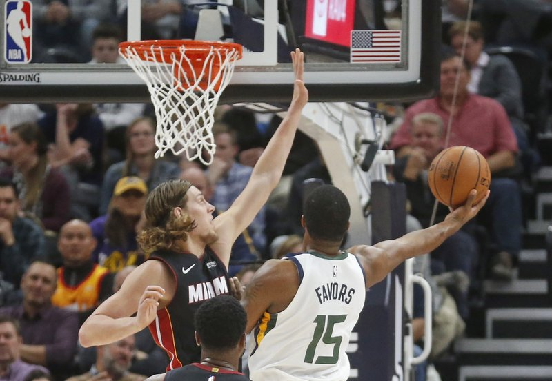 Utah Jazz forward Derrick Favors (15) lays the ball up as Miami Heat forward Kelly Olynyk, left, defends in the first half during an NBA basketball game Wednesday Dec. (AP Photo/Rick Bowmer)