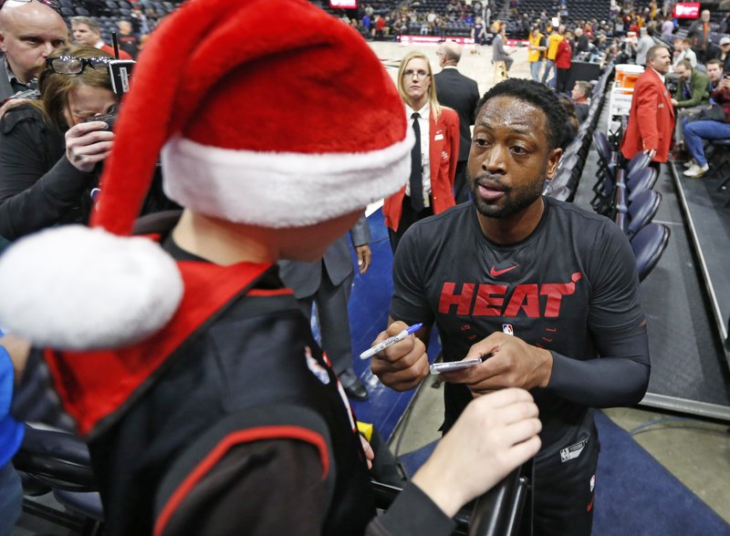 Miami Heat guard Dwyane Wade signs an autograph for a young fan before the start of their NBA basketball game against the Utah Jazz Wednesday Dec. (AP Photo/Rick Bowmer)