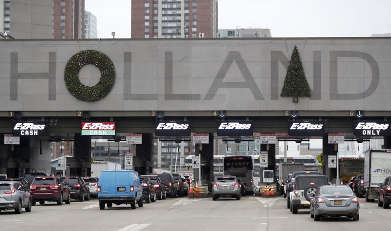 Holiday decorations adorn the letters on the toll booth structure on the Holland Tunnel approach, Thursday, Dec. (AP Photo/Julio Cortez)