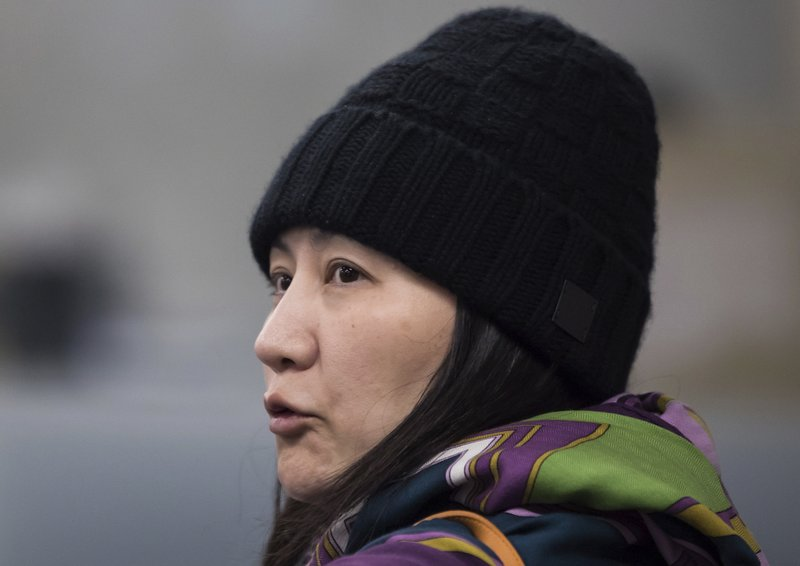 Huawei chief financial officer Meng Wanzhou talks with a member of her private security detail after they went into a wrong building while arriving at a parole office in Vancouver, British Columbia, Wednesday, Dec. (Darryl Dyck/The Canadian Press via AP)