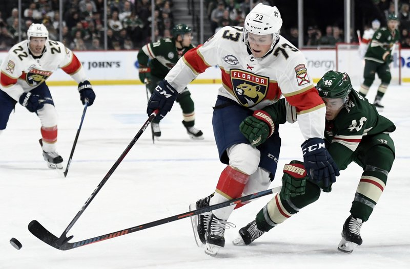 Minnesota Wild's Jared Spurgeon (46) knocks the puck away from Florida Panthers' Dryden Hunt (73) during the second period of an NHL hockey game Thursday, Dec. (AP Photo/Hannah Foslien)