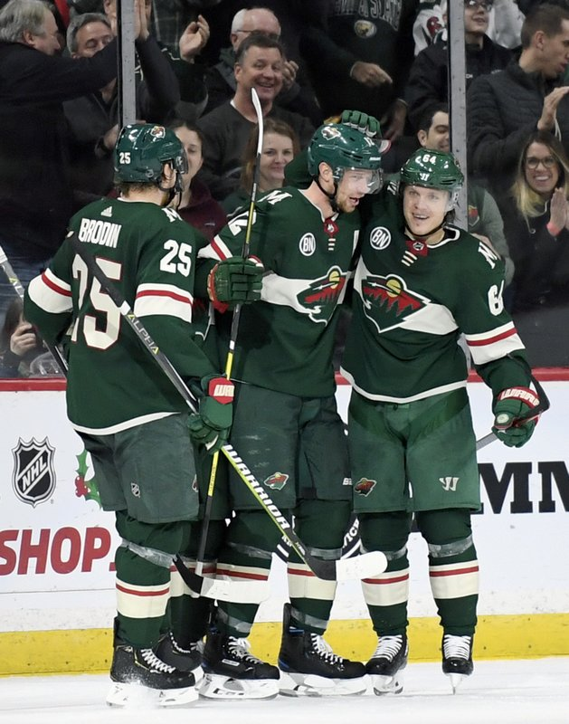 Minnesota Wild's Jonas Brodin (25), of Sweden, Eric Staal (12) and Mikael Granlund (64), of Finland, celebrate a goal by Staal against the Florida Panthers during the second period of an NHL hockey game Thursday, Dec. (AP Photo/Hannah Foslien)