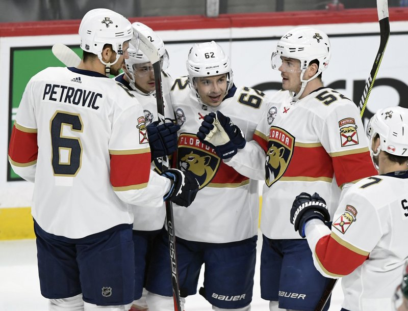 Florida Panthers' Alexander Petrovic (6), Frank Vatrano (72), Denis Malgin (62), of Switzerland, MacKenzie Weegar (52) and Colton Sceviour (7) celebrate a goal against the Minnesota Wild by Malgin during the first period of an NHL hockey game Thursday, Dec. (AP Photo/Hannah Foslien)