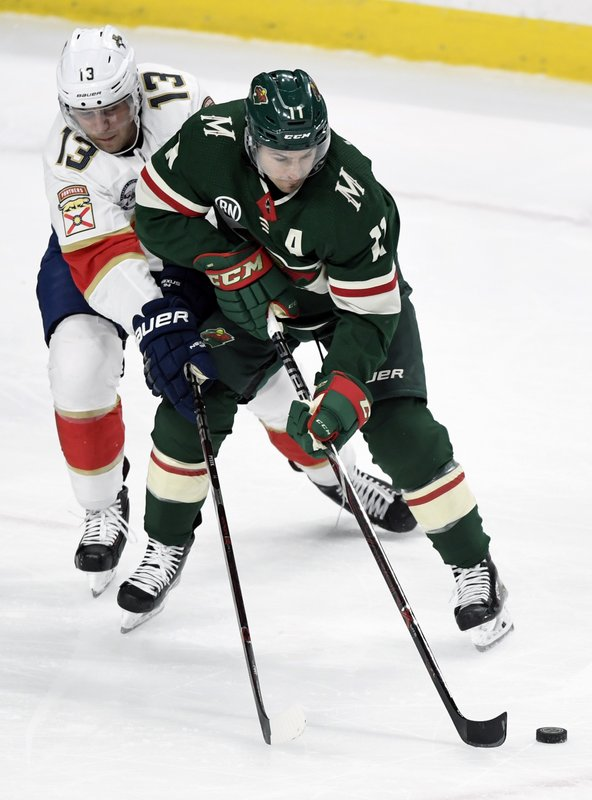 Florida Panthers defenseman Mark Pysyk (13) reaches for the puck controlled by Minnesota Wild left wing Zach Parise (11) during the first period of an NHL hockey game Thursday, Dec. (AP Photo/Hannah Foslien)