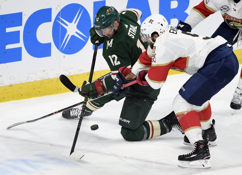 Minnesota Wild's Eric Staal (12) and Florida Panthers' Aaron Ekblad go after the puck during the first period of an NHL hockey game Thursday, Dec. (AP Photo/Hannah Foslien)
