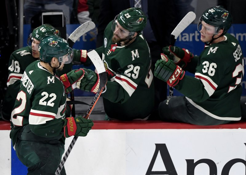 Minnesota Wild's Jared Spurgeon (46), Greg Pateryn (29) and Nick Seeler (36) congratulate teammate Nino Niederreiter (22), of Switzerland, on his goal against the Florida Panthers during the first period of an NHL hockey game Thursday, Dec. (AP Photo/Hannah Foslien)
