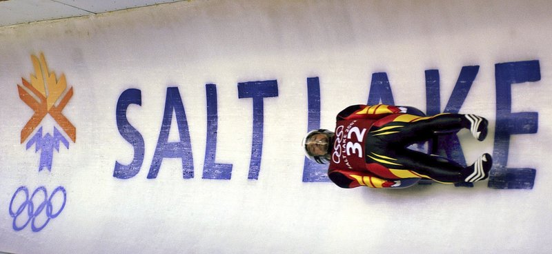 FILE - In this Feb. 9, 2002, file photo, Georg Hackl, of Germany, speeds past an Olympic logo during a practice run for the men's singles luge at the 2002 Salt Lake City Winter Olympics in Park City, Utah. (AP Photo/Elise Amendola, File)