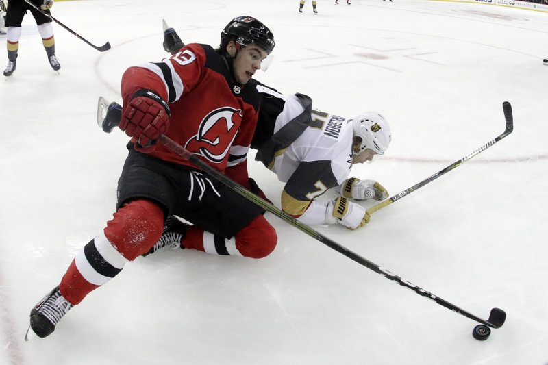 New Jersey Devils center Nico Hischier (13), of Switzerland, and Vegas Golden Knights center William Karlsson (71), of Sweden, fall to the ice while competing for the puck during the second period of an NHL hockey game, Friday, Dec. (AP Photo/Julio Cortez)