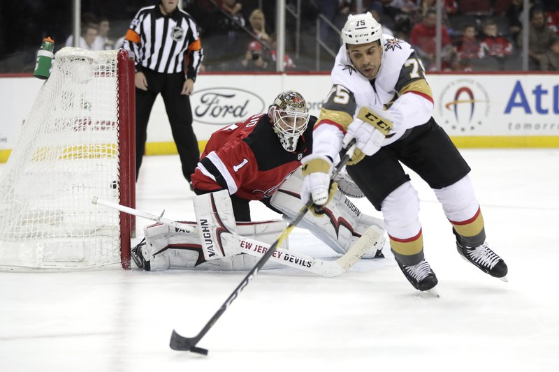New Jersey Devils goaltender Keith Kinkaid, left, keeps watch as Vegas Golden Knights right wing Ryan Reaves (75) controls the puck during the first period of an NHL hockey game, Friday, Dec. (AP Photo/Julio Cortez)