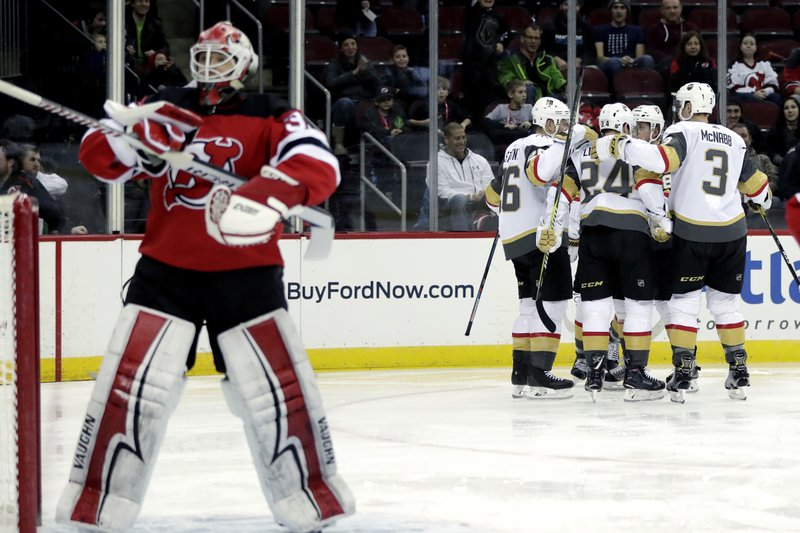 Vegas Golden Knights players, right, celebrate a goal by right wing Alex Tuch (89) on New Jersey Devils goaltender Cory Schneider, left, during the first period of an NHL hockey game, Friday, Dec. (AP Photo/Julio Cortez)
