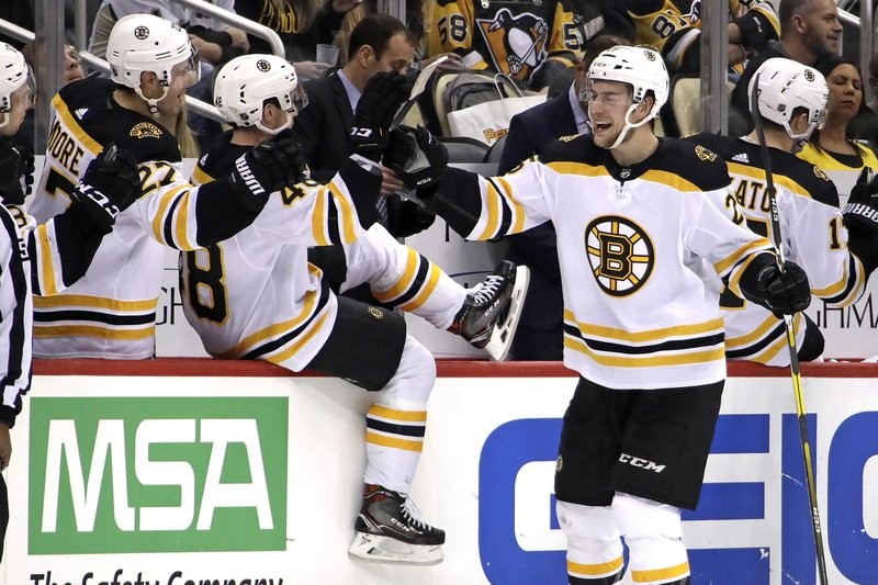 Boston Bruins' Brandon Carlo (25) celebrates as he returns to the bench after scoring during the second period of an NHL hockey game against the Pittsburgh Penguins in Pittsburgh, Friday, Dec. (AP Photo/Gene J. Puskar)