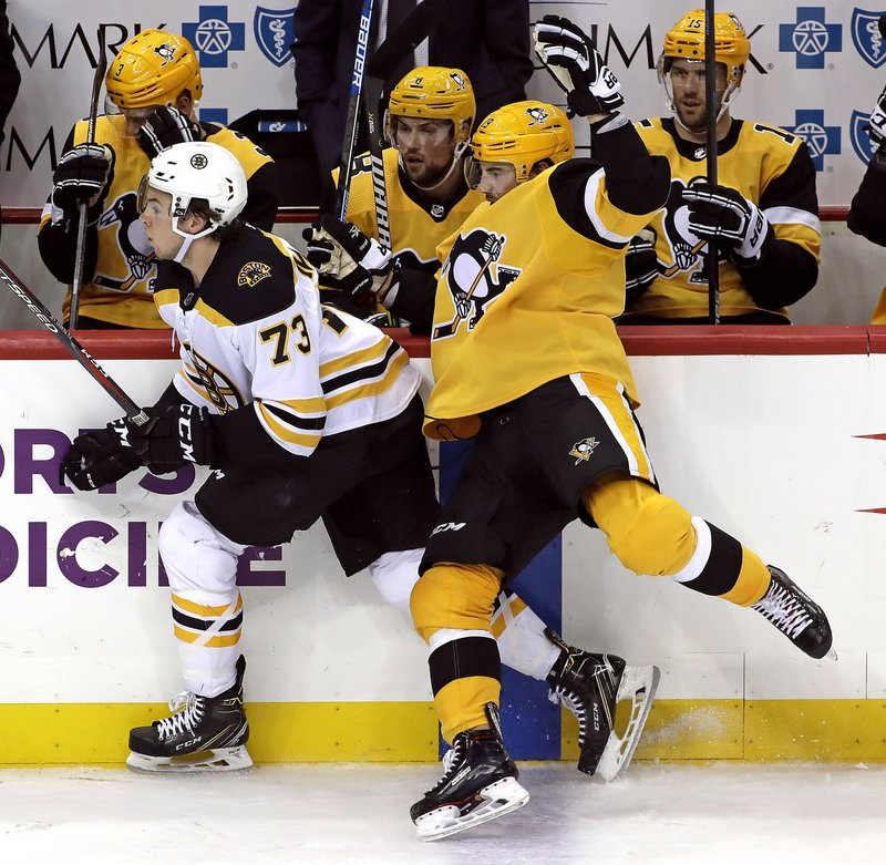 Pittsburgh Penguins' Zach Aston-Reese, right, collides with Boston Bruins' Charlie McAvoy (73) during the first period of an NHL hockey game in Pittsburgh, Friday, Dec. (AP Photo/Gene J. Puskar)