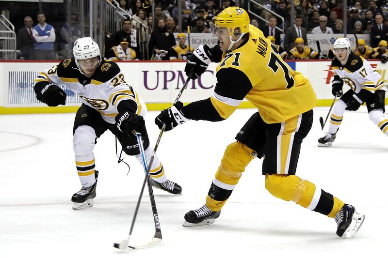 Pittsburgh Penguins' Evgeni Malkin (71) gets off a shot with Boston Bruins' Jakob Forsbacka Karlsson (23) defending during the second period of an NHL hockey game in Pittsburgh, Friday, Dec. (AP Photo/Gene J. Puskar)