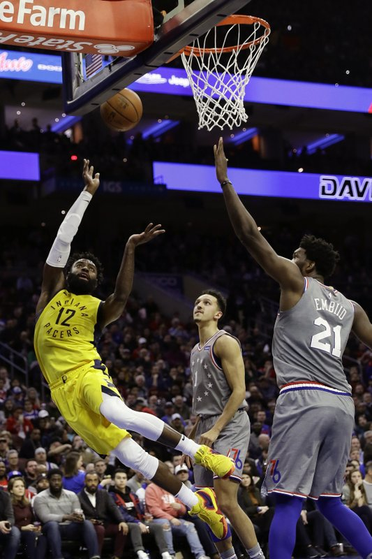 Indiana Pacers' Tyreke Evans, left, goes up to shoot against Philadelphia 76ers' Joel Embiid, right, as Landry Shamet watches during the first half of an NBA basketball game, Friday, Dec. (AP Photo/Matt Slocum)