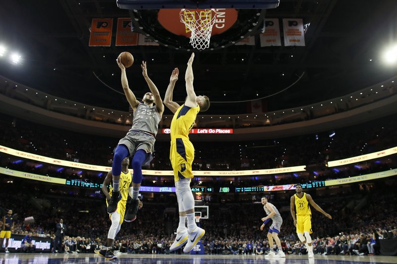 Philadelphia 76ers' Ben Simmons, left, goes up for a shot against Indiana Pacers' Domantas Sabonis during the first half of an NBA basketball game, Friday, Dec. (AP Photo/Matt Slocum)