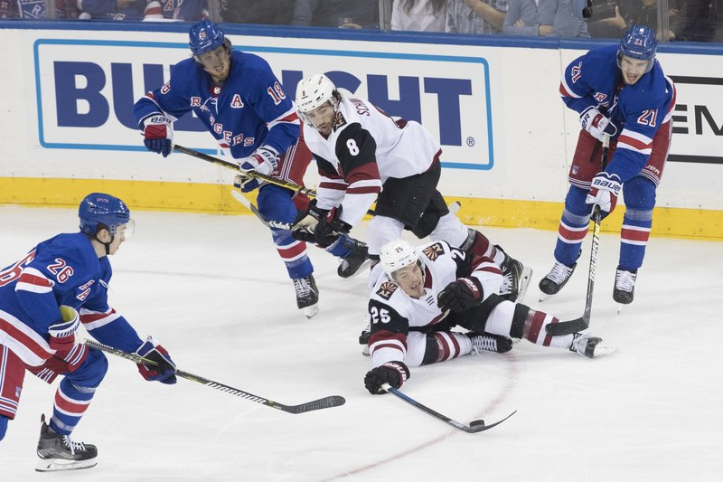 Arizona Coyotes center Nick Cousins (25) controls the puck skating against New York Rangers left wing Jimmy Vesey (26) and center Brett Howden (21) during the third period of an NHL hockey game, Friday, Dec. (AP Photo/Mary Altaffer)