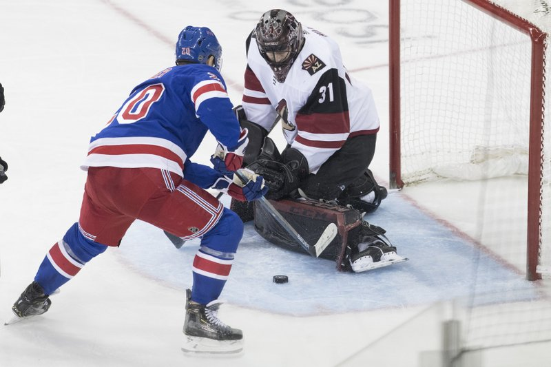 Arizona Coyotes goaltender Adin Hill (31) makes the save against New York Rangers left wing Chris Kreider (20) during the third period of an NHL hockey game, Friday, Dec. (AP Photo/Mary Altaffer)