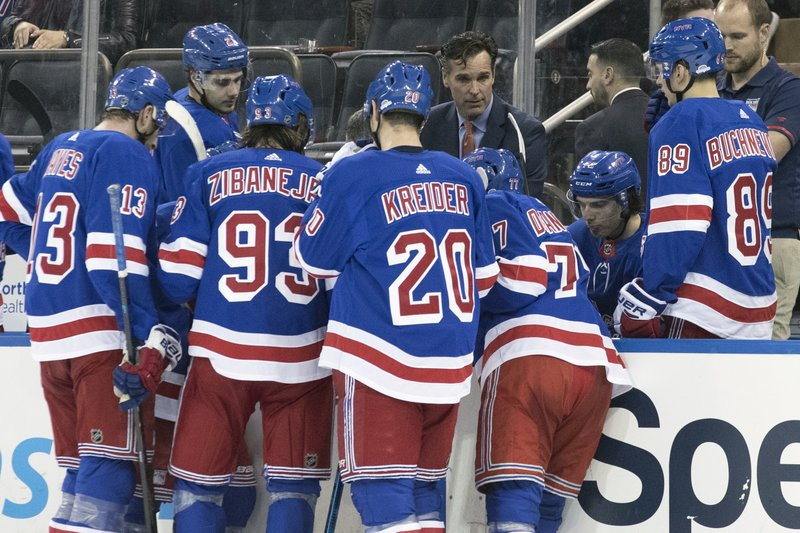 New York Rangers head coach David Quinn, facing camera, gives his team instruction during a time out in the second period of an NHL hockey game, Friday, Dec. (AP Photo/Mary Altaffer)