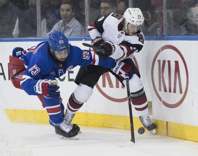 New York Rangers center Mika Zibanejad (93) fights for the puck against Arizona Coyotes right wing Mario Kempe (29) during the second period of an NHL hockey game, Friday, Dec. (AP Photo/Mary Altaffer)
