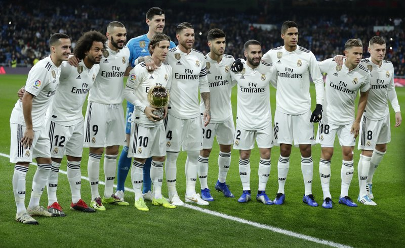 Real Madrid's Luka Modric holds his Ballon d'Or (Golden Ball) award as European Footballer of the Year as he poses with his teammates prior of he Spanish La Liga soccer match between Real Madrid and Rayo Vallecano at the Bernabeu stadium in Madrid, Spain, Saturday, Dec. (AP Photo/Manu Fernandez)