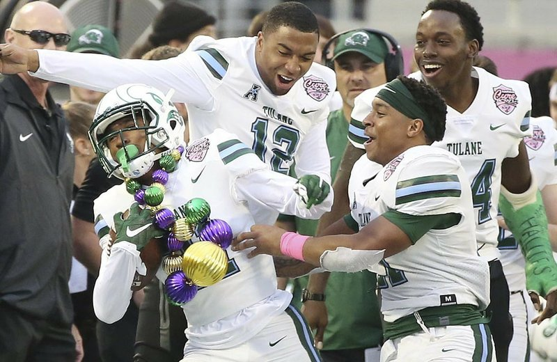 Tulane defensive back Chris Joyce (wearing ornament necklace) celebrates with teammates after an interception during the Cure Bowl NCAA college football game against Louisiana in Orlando, Fla, on Saturday, Dec. (Stephen M. Dowell/Orlando Sentinel via AP)