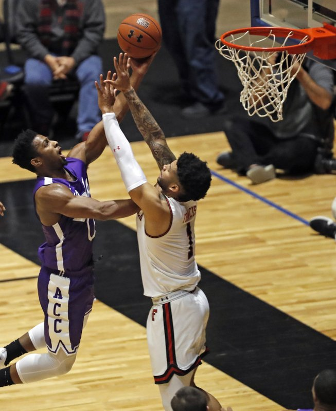 Abilene Christian's Jaylen Franklin (0) tries to shoot the ball around Texas Tech's Brandone Francis (1) during the first half of an NCAA college basketball game Saturday, Dec. (AP Photo/Brad Tollefson)