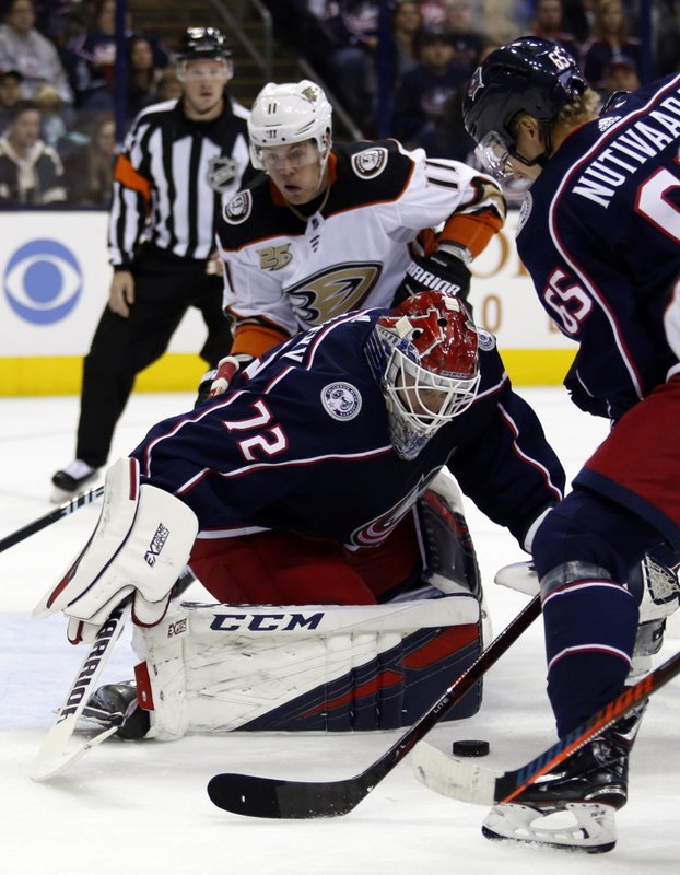 Columbus Blue Jackets goalie Sergei Bobrovsky, center, of Russia, stops a shot between Anaheim Ducks forward Daniel Sprong, left, of the Netherlands, and Blue Jackets defenseman Markus Nutivaara, of Finland, during the first period of an NHL hockey game in Columbus, Ohio, Saturday, Dec. (AP Photo/Paul Vernon)