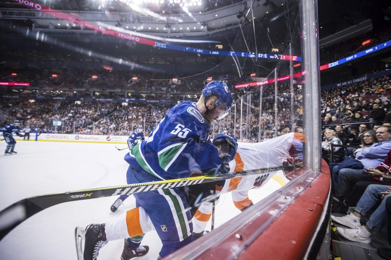 Vancouver Canucks' Alex Biega, front left, checks Philadelphia Flyers' Jori Lehtera, of Finland, during the first period of an NHL hockey game in Vancouver, British Columbia, on Saturday, Dec. (Darryl Dyck/The Canadian Press via AP)