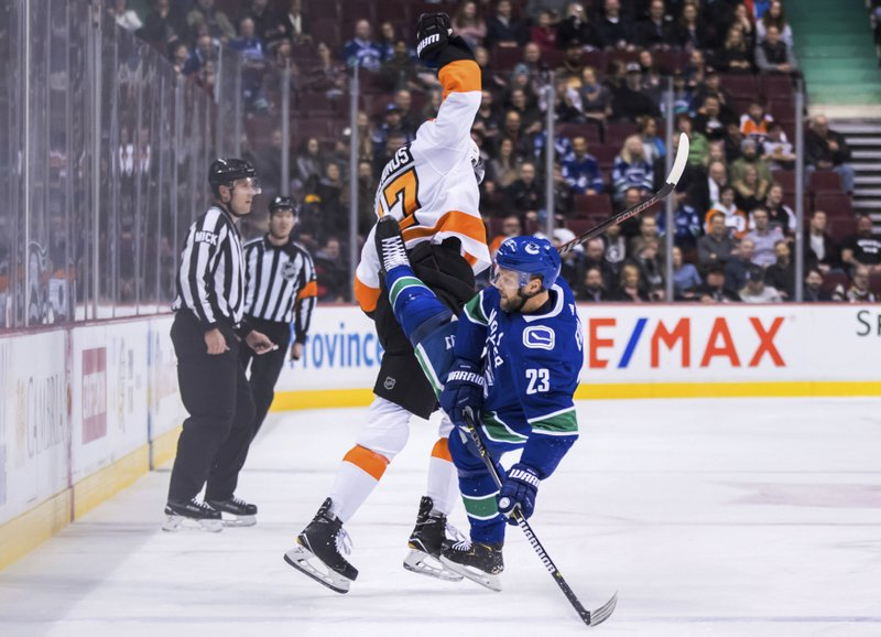 Philadelphia Flyers' Wayne Simmonds, back, and Vancouver Canucks' Alexander Edler, of Sweden, collide during the first period of an NHL hockey game in Vancouver, British Columbia, on Saturday, Dec. (Darryl Dyck/The Canadian Press via AP)