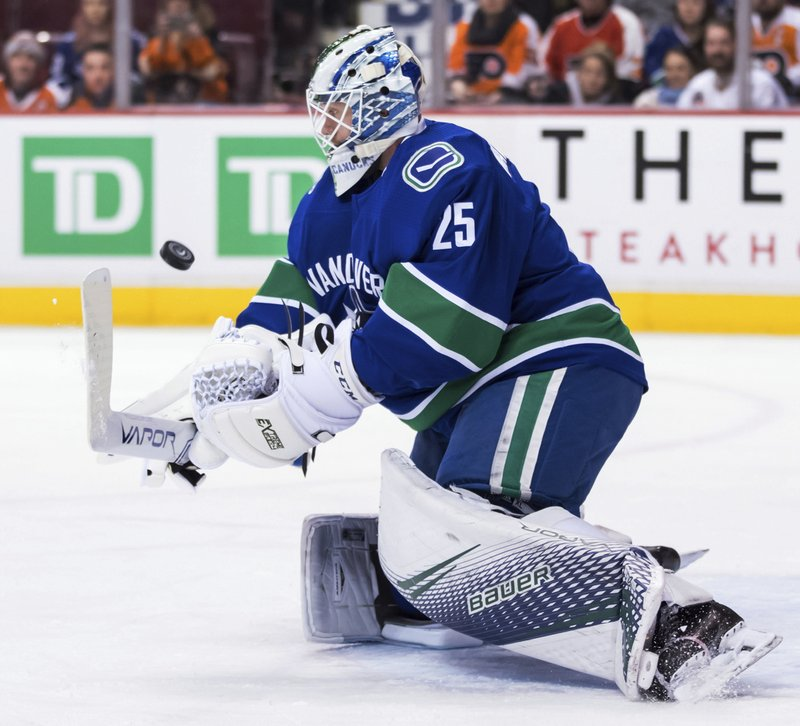 Vancouver Canucks goalie Jacob Markstrom, of Sweden, makes a save during the first period of an NHL hockey game against the Philadelphia Flyers in Vancouver, British Columbia, on Saturday, Dec. (Darryl Dyck/The Canadian Press via AP)
