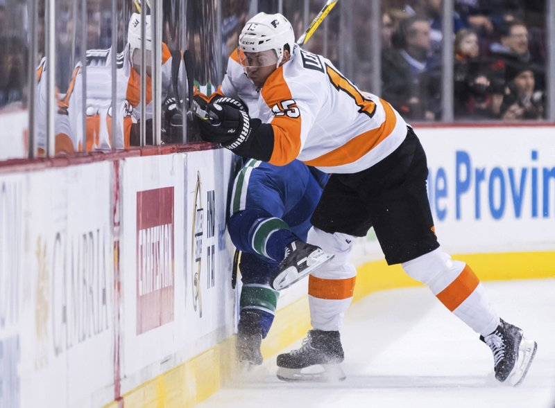 Philadelphia Flyers' Jori Lehtera, front right, of Finland, misses the check on Vancouver Canucks' Alex Biega during the first period of an NHL hockey game in Vancouver, British Columbia, on Saturday, Dec. (Darryl Dyck/The Canadian Press via AP)