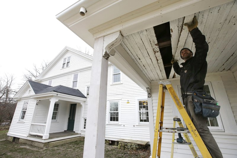 In this Thursday, Dec. 13, 2018 photo, carpenter Jeremy Parker works on a porch at the conclusion of a restoration of the home where Sarah Clayes lived in Framingham, Mass. (AP Photo/Steven Senne)