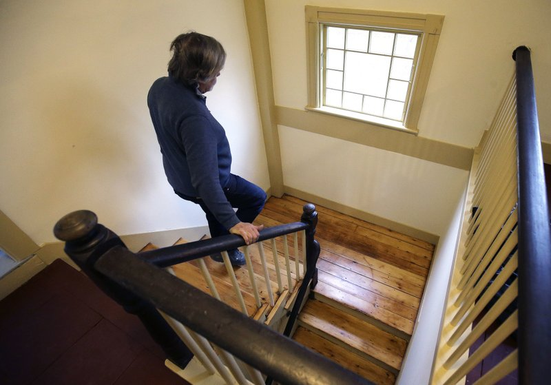 In this Thursday, Dec. 13, 2018 photo, builder Ned Murphy descends a staircase at the home where Sarah Clayes lived, in Framingham, Mass. (AP Photo/Steven Senne)