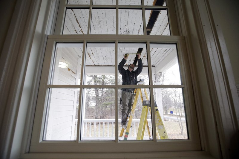 In this Thursday, Dec. 13, 2018 photo, carpenter Jeremy Parker works on a porch at the conclusion of a restoration of the home where Sarah Clayes lived, in Framingham, Mass. (AP Photo/Steven Senne)