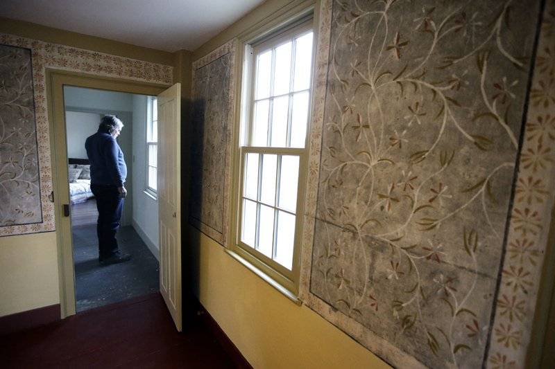 In this Thursday, Dec. 13, 2018 photo builder Ned Murphy stands near a window outside a room that features historic paint-on-plaster murals at the home where Sarah Clayes lived, in Framingham, Mass. (AP Photo/Steven Senne)