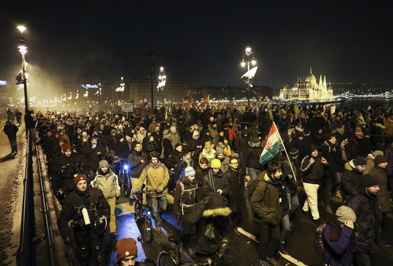 Anti-government demonstrators march across Margaret Bridge over the River Danube with the Parliament building in the background, in Budapest, Hungary, Sunday, Dec. (Balazs Mohai/MTI via AP)
