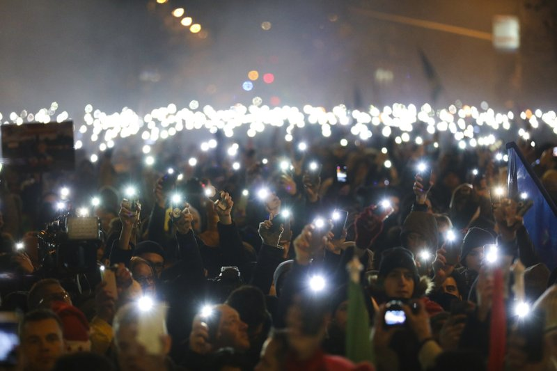 Anti-government demonstrators light up their mobile phones during their protest in the downtown of Budapest, Hungary, Sunday, Dec. (Balazs Mohai/MTI via AP)