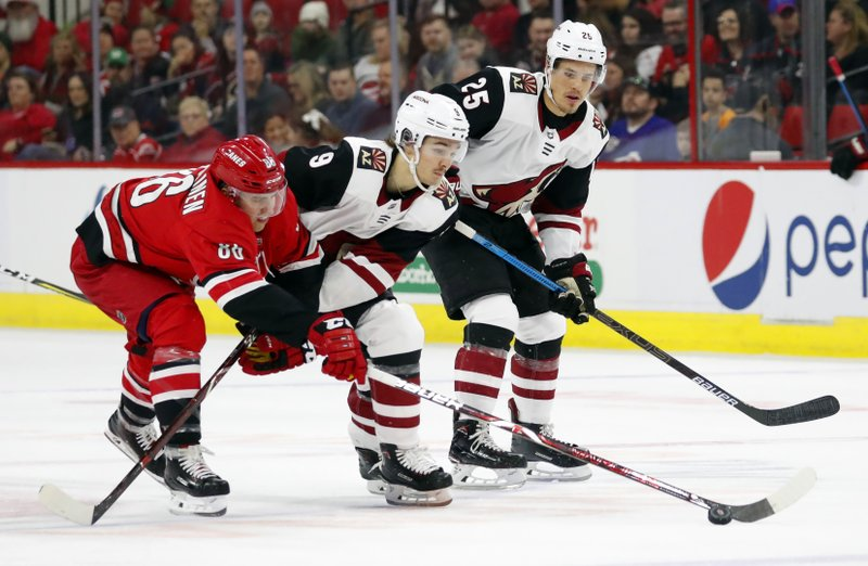 Carolina Hurricanes' Teuvo Teravainen (86) tips the puck away from Arizona Coyotes' Clayton Keller (9) with Coyotes' Nick Cousins (25) looking on during the first period of an NHL hockey game, Sunday, Dec. (AP Photo/Karl B DeBlaker)