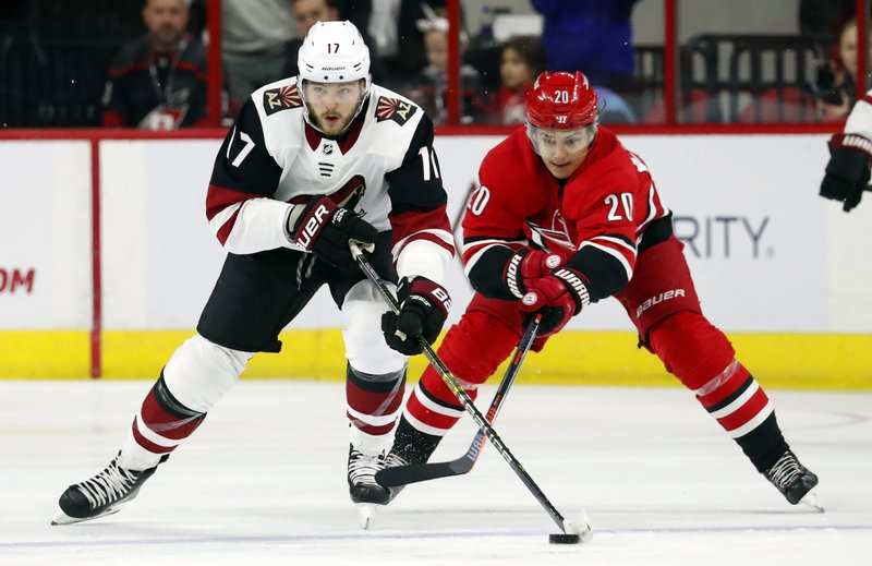 Arizona Coyotes' Alex Galchenyuk (17) keeps the puck away from Carolina Hurricanes' Sebastian Aho (20) during the first period of an NHL hockey game, Sunday, Dec. (AP Photo/Karl B DeBlaker)