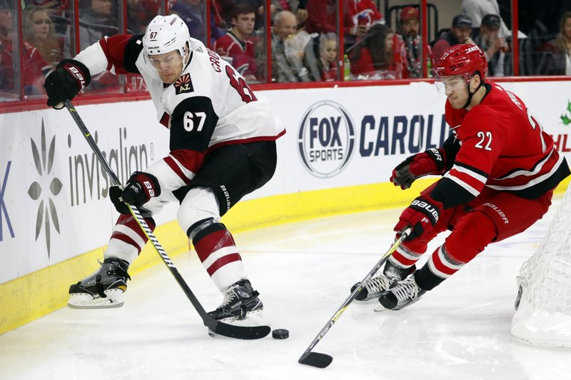 Arizona Coyotes' Lawson Crouse (67) battles behind the net with Carolina Hurricanes' Brett Pesce (22) during the second period of an NHL hockey game, Sunday, Dec. (AP Photo/Karl B DeBlaker)