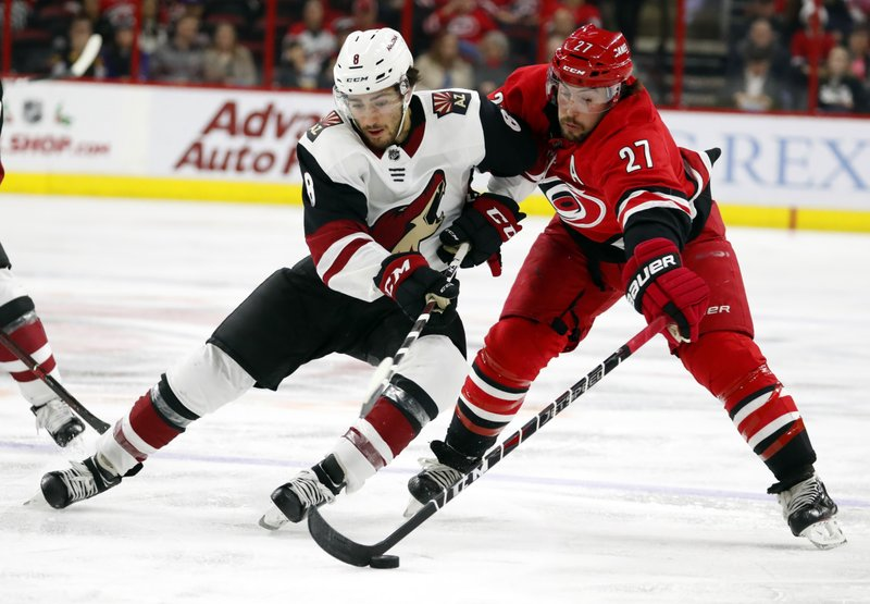Arizona Coyotes' Nick Schmaltz (8) has the puck taken away by Carolina Hurricanes' Justin Faulk (27) during the second period of an NHL hockey game, Sunday, Dec. (AP Photo/Karl B DeBlaker)