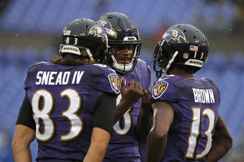 Baltimore Ravens quarterback Lamar Jackson, center, speaks with teammates Willie Snead, left, and John Brown before an NFL football game against the Tampa Bay Buccaneers, Sunday, Dec. (AP Photo/Carolyn Kaster)