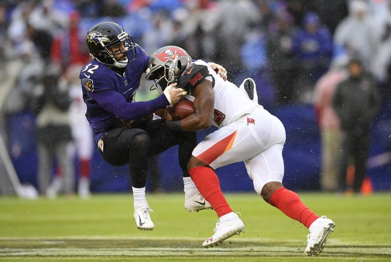 Tampa Bay Buccaneers running back Peyton Barber, right, rushes against Baltimore Ravens free safety Eric Weddle in the first half of an NFL football game, Sunday, Dec. (AP Photo/Nick Wass)