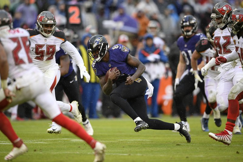 Baltimore Ravens quarterback Lamar Jackson, center, rushes the ball in the second half of an NFL football game against the Tampa Bay Buccaneers, Sunday, Dec. (AP Photo/Nick Wass)