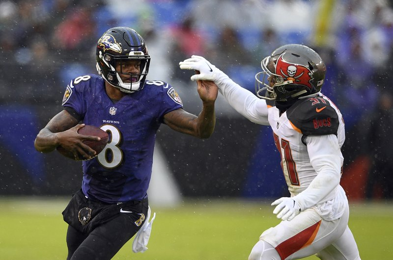 Baltimore Ravens quarterback Lamar Jackson, left, rushes against Tampa Bay Buccaneers free safety Jordan Whitehead in the first half of an NFL football game, Sunday, Dec. (AP Photo/Nick Wass)